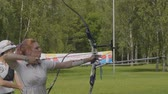 longbow : BARNAUL - AUGUST 6: Attractive female archer bending a bow and aiming in the target on August 6, 2017 in Barnaul, Russia.