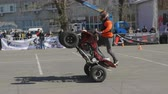 both : MOSCOW - MAY 15, 2018: Stunt rider making wheelie while rides on the rear wheel on May 15, 2018 in Moscow, Russia