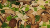 Tasty organic mushrooms with spring onions in a pan