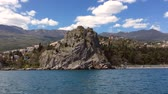 Big old rocks and thick pine forests on seashore in Crimea shot from moving boat