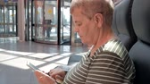 Close up of senior woman holding and using modern smartphone in business shopping center in front of revolving doors. Concept of elderly people and modern technology