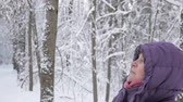 Close up of senior woman in winter jacket with hood looking up, smiling and admiring beauty of winter forest covered with fresh snow