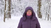 Close up of attractive senior woman in winter jacket with hood walking forward, looking into camera and smiling in winter forest covered with snow.