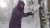 Senior woman in winter jacket with hood picking up handful of fresh fluffy snow from ground and blowing snow flakes in winter forest