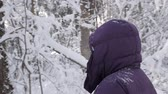 Close up of senior woman wearing winter jacket with hood and walking past camera in beautiful winter forest, covered with white fresh snow on a sunny day Vídeos