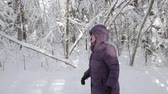 Senior woman in winter jacket and hood walking in profile Vídeos