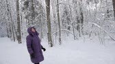Senior woman in winter jacket with hood looking up, admiring beauty of winter forest covered with fresh snow