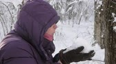 Close up of a senior woman in a winter jacket and hood with a handful of fresh fluffy snow in gloves, blowing snow flakes in a winter forest.