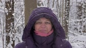 Close up of attractive senior woman in winter jacket and hood looking straight into camera and smiling in winter. Vídeos
