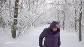 Senior woman wearing a winter jacket and hood shaking a snow on a white background