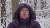 Close up of an attractive senior woman in a winter jacket and hood looking into a camera and blowing a steam from her mouth in a cold winter forest covered with snow.