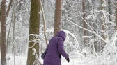 Woman in winter jacket with hood walking with difficulty.