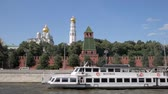parede : MOSCOW - AUGUST 17, 2018: Tourist ships passing by red brick Kremlin walls, towers and beautiful white churches in Moscow, Russia Stock Footage