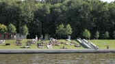 banhos de sol : Beautiful Moskva river embankment on Sparrow Hills with lush green trees, summer beach and people lying on loungers and enjoying hot summer in Moscow, Russia