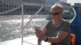 navigatie : Mature woman sitting on tourist ship and holding smartphone with sparkling water and tourist boat passing behind on sunny summer day Stockvideo