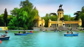 Tourists and citizens relax and swim in boats in the park of Buen Retiro in Madrid.