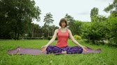 fitness : The young blonde girl practicing yoga in the park. The Lotus posture. Meditation