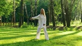 quimono : A young woman practicing qigong rotating steel sword around her body. Slow motion. HD