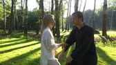 quimono : Training in the park. Workout. Blond woman and young man practicing qigong. 4K