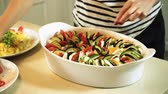 espalhando : Cooking ratatouille. Female hands laying out the chopped vegetables in a baking dish. HD