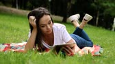 dark haired : The young pretty slender dark-haired woman using digital tablet in the spring park. HD