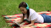 charming : Pretty dark-haired young woman using digital tablet for listening to the music on headphones in the park on a sunny day. HD Stock Footage