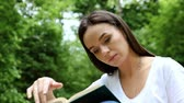 dark haired : Portrait of a beautiful young dark woman reading a book in a spring park. HD Stock Footage