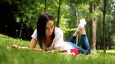 dark haired : Young pretty dark-haired woman eating an apple and reading a book lying on the grass in a park. HD