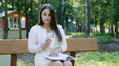 nealkoholické : Young pretty woman drinking coffee and reading a book on a bench in a summer park. 4K