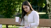 não alcoólica : Young pretty woman drinking coffee and reading a book on a bench in a summer park. 4K