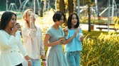 quatro pessoas : Four young beautiful women walking in the park, talking and drinking coffee. Slow motion. HD