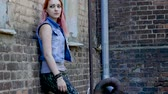 goth : Teenage girl with nose piercing and pink hair standing on brick wall background. Slow motion. HD