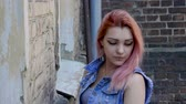 perfurante : Teenage girl with nose and lips piercing and pink hair standing on brick wall background. Slow motion. HD Stock Footage