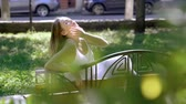 cabelos lisos : Attractive elegant young woman in a white dress sitting on a wood bench and looking at camera on the summer street. Slow motion. HD