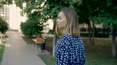 cabelos lisos : Beautiful young woman walking down the city street, turning to camera and giving a lovely playful smile. 4K Stock Footage