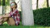 uzun saçlı : Beautiful young woman in sunglasses sitting under the tree on the green grass at city park. 4K