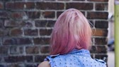 goth : View from the back of young trendy teenage girl with pink hair. Slow motion. HD