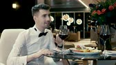 tailcoat : The handsome man smiling, talking with his girlfriend and drinking red wine in a modern restaurant. 4K Stock Footage