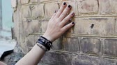 goth : Womens hand with a black wristband moving along the brick wall. Slow motion. HD