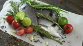 seabass : Ingredients for cooking fish. Fresh sea bass, green onions, lime, garlic cloves, rosemary, seasoning. 4K Stock Footage