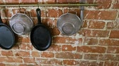 strainer : Kitchen interior. Panorama of cast iron frying pans, sieves, whisk, wooden cutting boards on brick wall background. 4K
