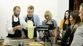 мастер : Chef showing men and women how to roll out dough for macaroni using the pasta machine. 4K