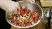 песто : Mens hands stirring pesto sauce, chopped tomatoes, garlic and grated almonds in bowl. 4K