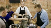 mexilhões : A group of people preparing mussels with cream at the cooking master class. 4K