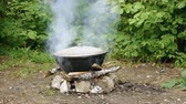 elenco : Cooking outdoors. Medium shot of a large cast-iron cauldron on open fire. 4K
