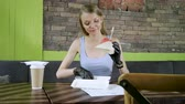 lanchonete : A young woman wearing black rubber gloves and going to eat a hamburger and drink coffee. 4K