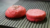 szezámmag : Red bun. Close-up shot of two halves of hamburger bread are being fried on a grill for burger. 4K Stock mozgókép