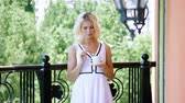 střední : Beautiful young blonde woman in white dress drinking coffee, standing on the balcony of a luxury hotel. 4K