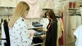 butik : Two happy young girls are choosing clothes in a department store. 4K