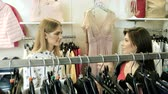бутик : Two happy young girls are choosing clothes in a department store. 4K